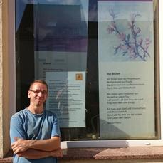 Gisbert Amm vor dem Schaufenster des Lyrikhauses. Foto: Jos Delisse